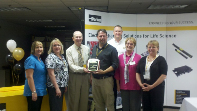 Accepting the award from members of Parker Hannifin are Plant Manager David Kvamme and Sales Manager Duncan Larson.